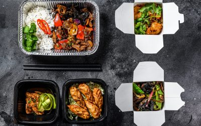 Spring rolls, dumplings, gyoza and wok noodles in Take away box.